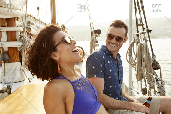 Man looking at happy girlfriend while enjoying on boat during summer