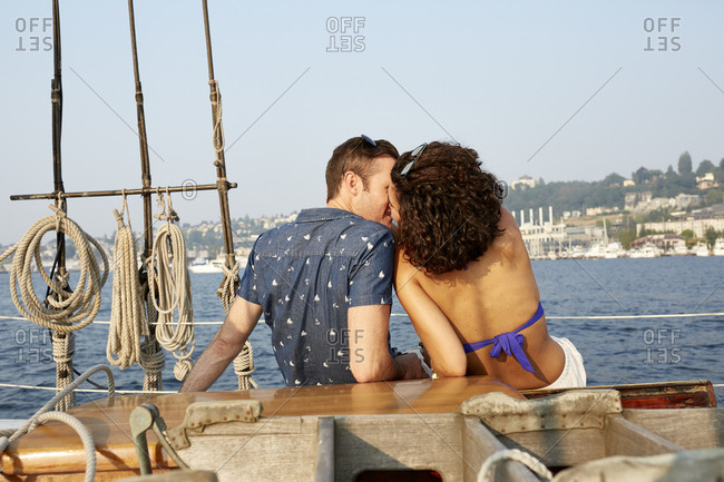 Rear view of loving man kissing woman while sitting on boat against sky
