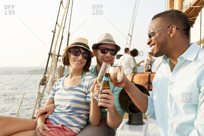 Happy male friend toasting drinks with couple while sitting in sailboat