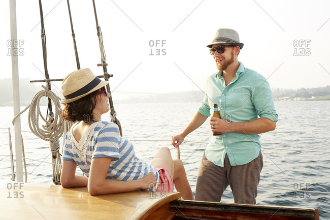 Happy man with beer bottle talking to girlfriend while enjoying on boat during summer