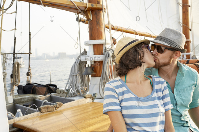 Loving man kissing woman while sitting on boat against sky during summer