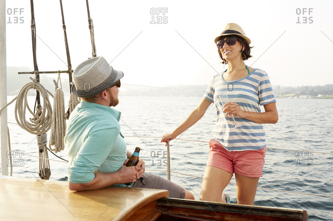 Smiling woman talking to boyfriend while enjoying on boat during summer