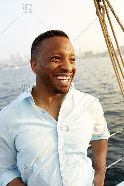 Cheerful mid adult man standing in boat against sea during summer