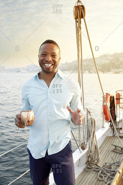 Happy mid adult man holding mug while standing in boat against sky