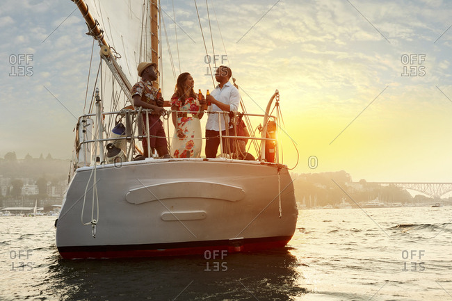 Low angle view of male and female friends enjoying beer on boat over sea against sky during sunset