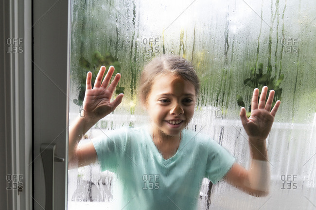 Girl pressing her face and hands against sliding glass door covered in condensation
