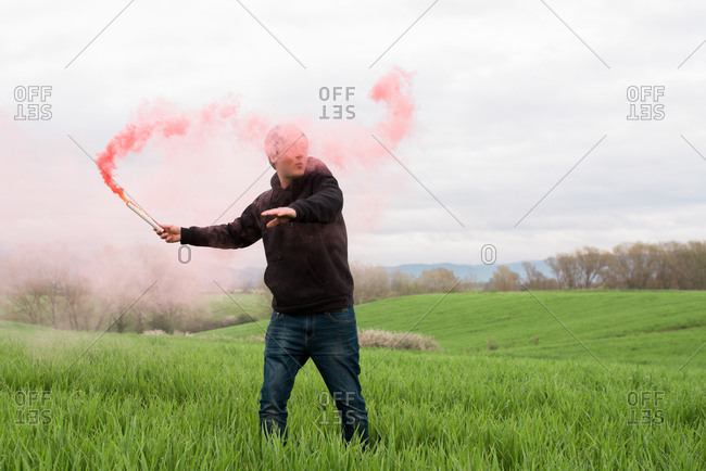 Man with flare in middle of field