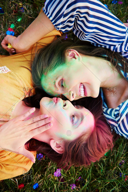Two young women covered in coloured chalk powder lying on grass at Holi Festival, overhead view