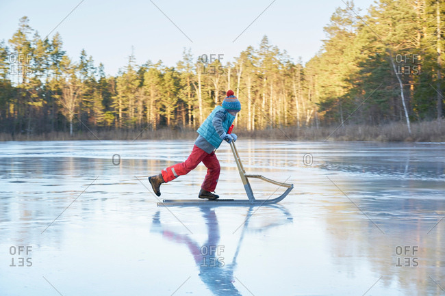 Boy skating on sleigh across frozen lake