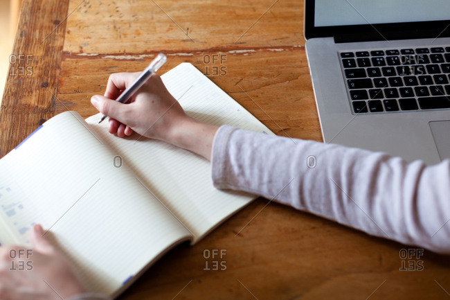 Woman writing notes into notepad from laptop