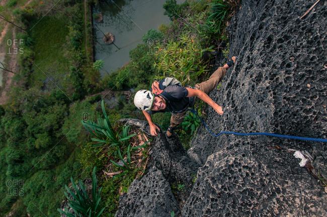 Man rock climbing Guilin Sugarloaf, high angle view, Yangshuo, Guangxi, China