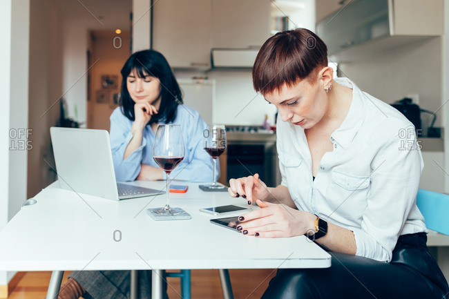 Women sitting at table using laptop and digital tablet