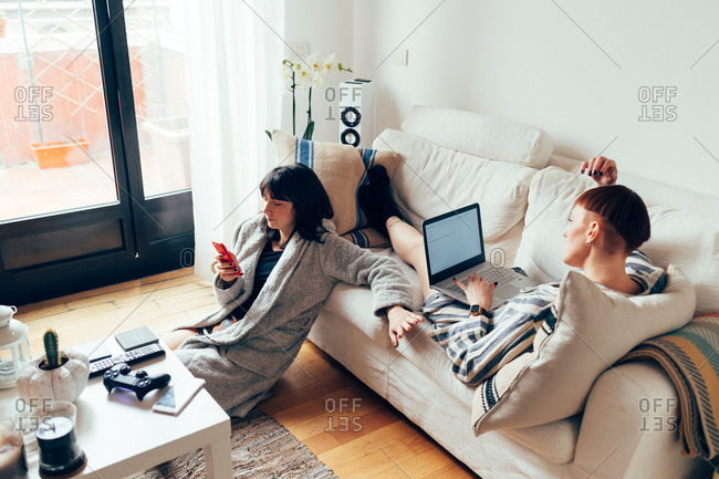Women relaxing on sofa using laptop and mobile phone