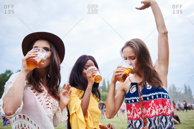 Friends drinking and dancing with arms raised in music festival
