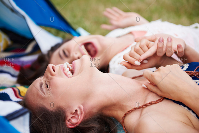 Friends lying on ground, laughing and enjoying music festival
