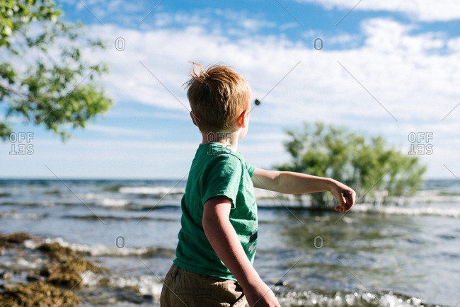 Boy throwing stone into water, Kingston, Canada