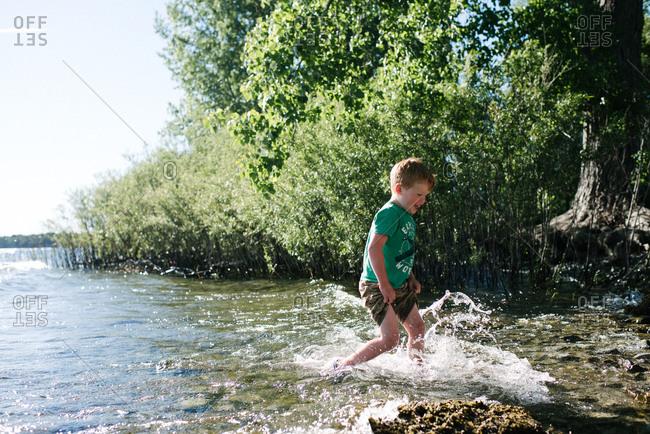 Boy running in water, Kingston, Canada