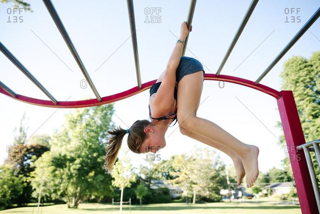 Girl on horizontal ladder climber in playground, Kingston, Canada