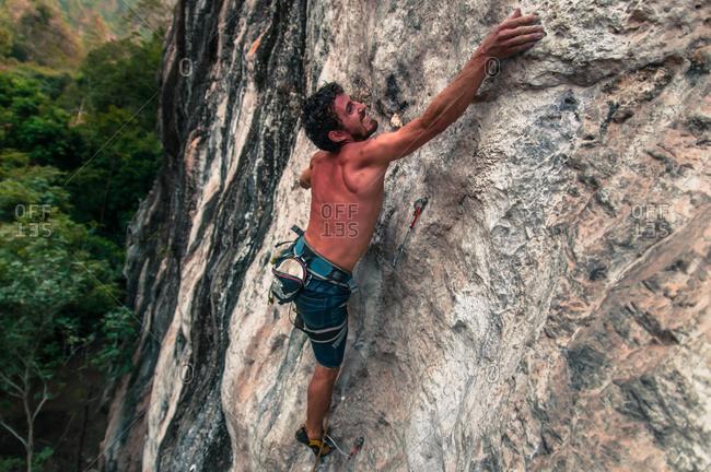 Man sport climbing on limestone, Thakhek, Laos