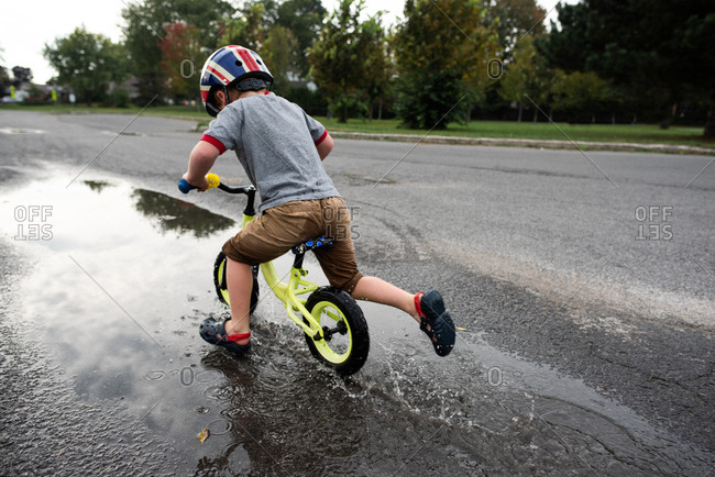 Boy riding bicycle on wet road