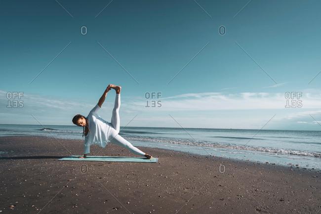 Woman practicing yoga on beach