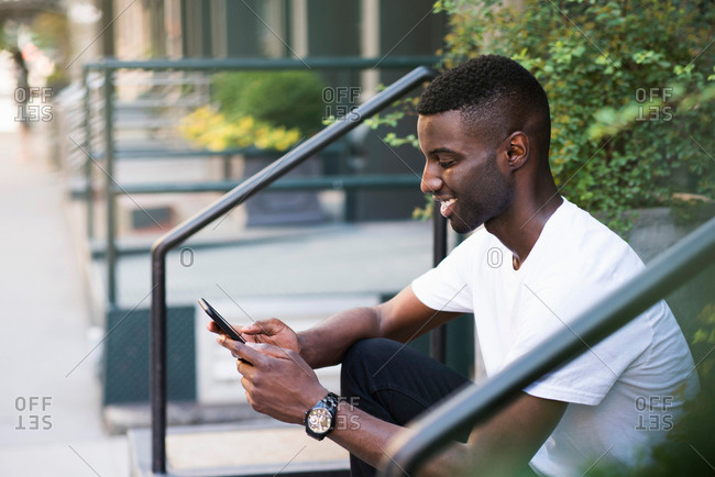 Young man using cellphone on step in streets of New York, US