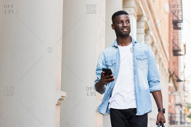 Young man with hand luggage holding cellphone in streets of New York, US