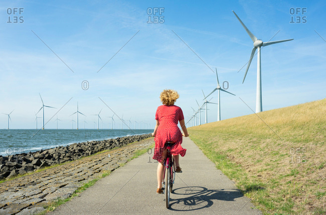 Girl cycling between onshore and offshore wind farm, Urk, Flevoland, Netherlands