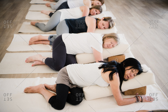 Women in relaxation pose after yoga class at retreat