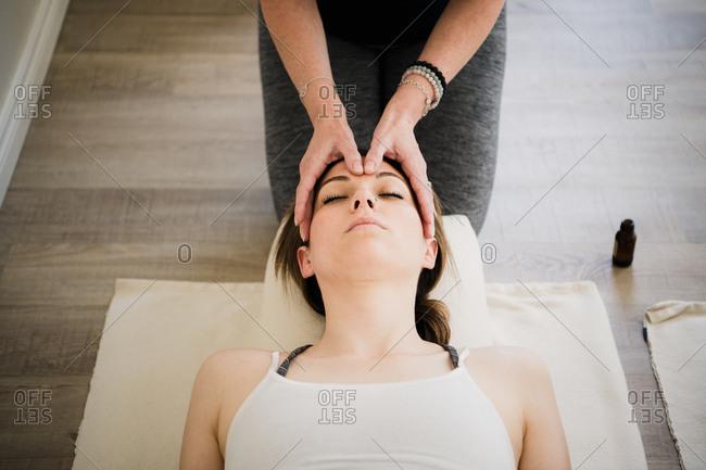 Woman enjoying head massage in yoga retreat