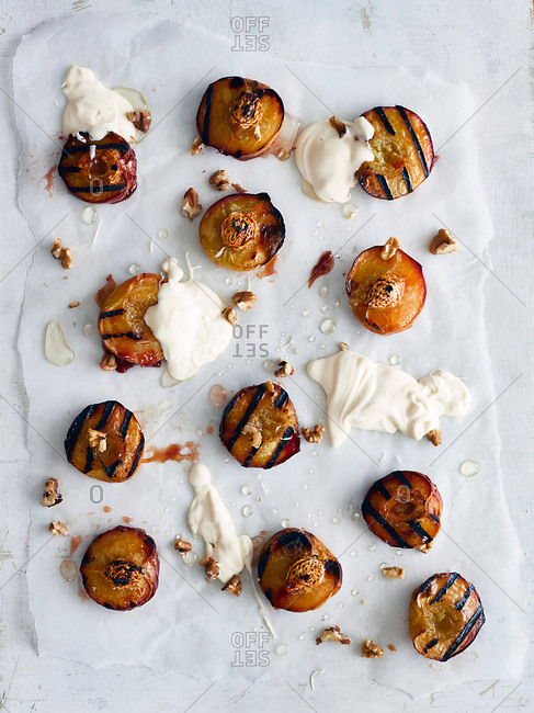 Roasted peaches on baking sheet with cream