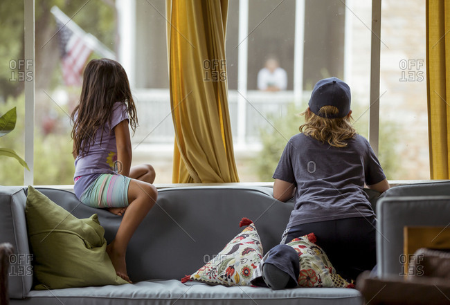 Children sitting on couch and looking out window at their neighbors