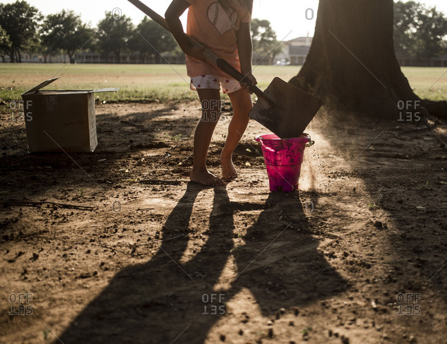 Child using a large shovel to fill a bucket with dirt in the yard