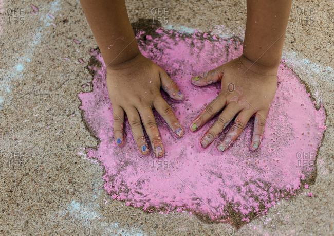 Child pressing hands into wet sidewalk chalk