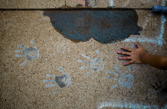 Child making handprints with wet sidewalk chalk
