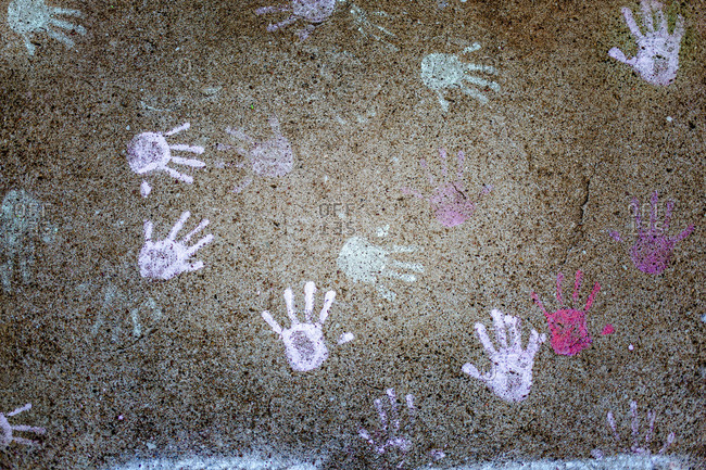Colorful chalk handprints of children on sidewalk