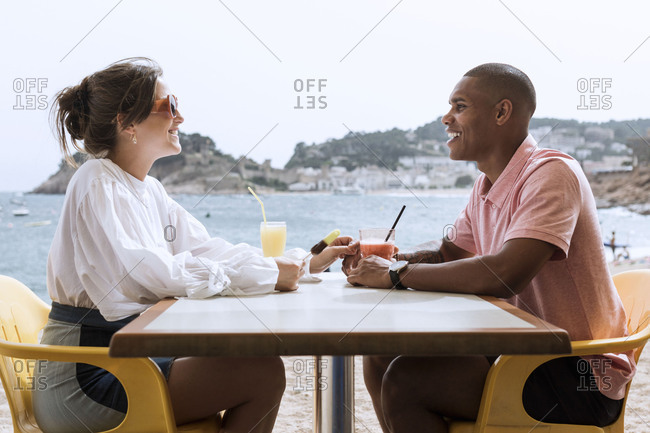 An interracial couple has a drink on the beach