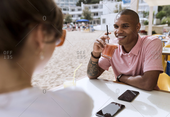 Man smiling across the table from a woman on the beach