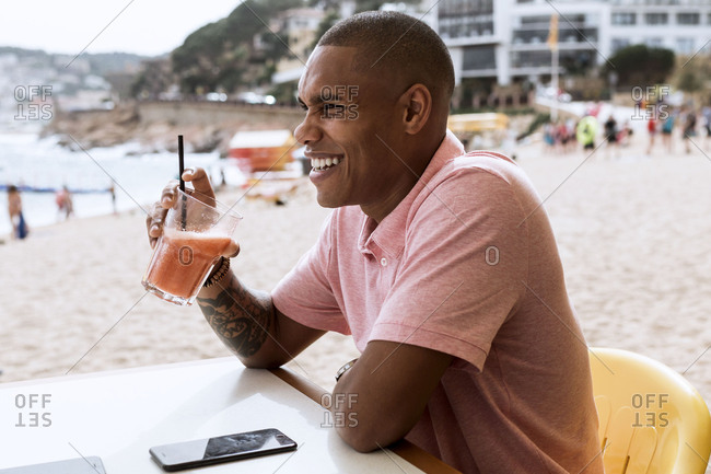 Man laughing with daiquiri at a table on the beach