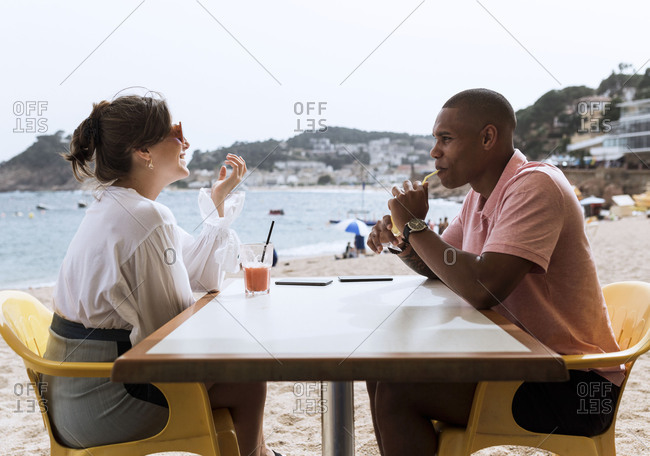 An interracial couple chatting at a beach table