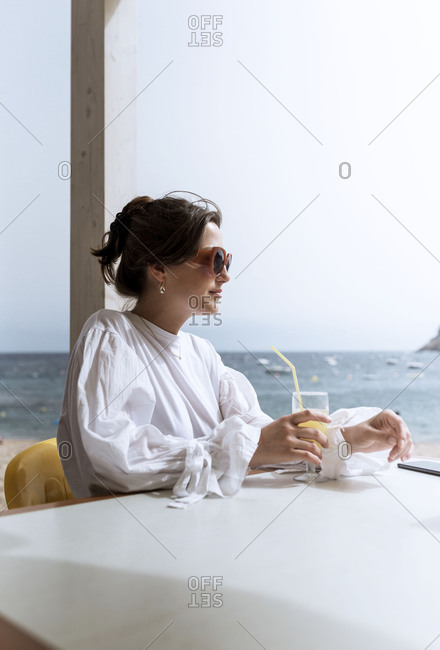 Woman in a flowy white shirt sitting alone at a beach side restaurant