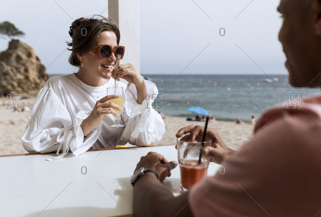 An interracial couple flirting over drinks on the beach