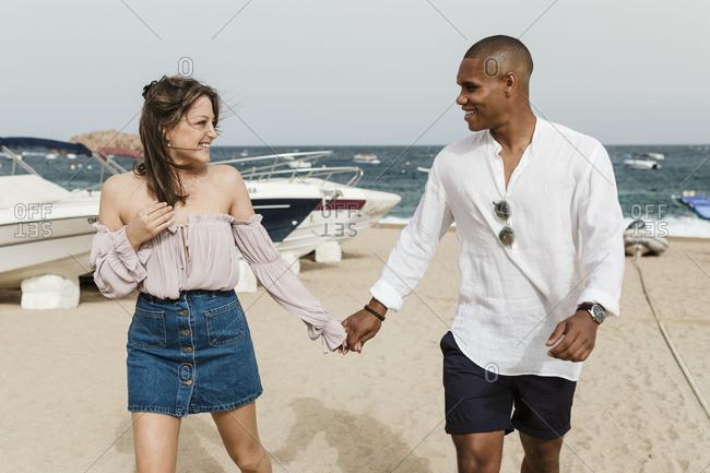 An interracial couple walks on the beach holding hands