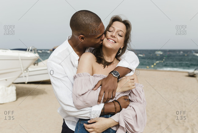 An interracial couple embraces on the beach