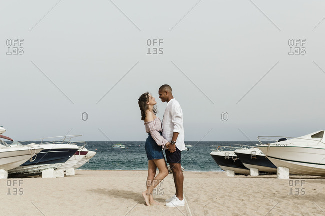 An interracial couple facing each other on the beach