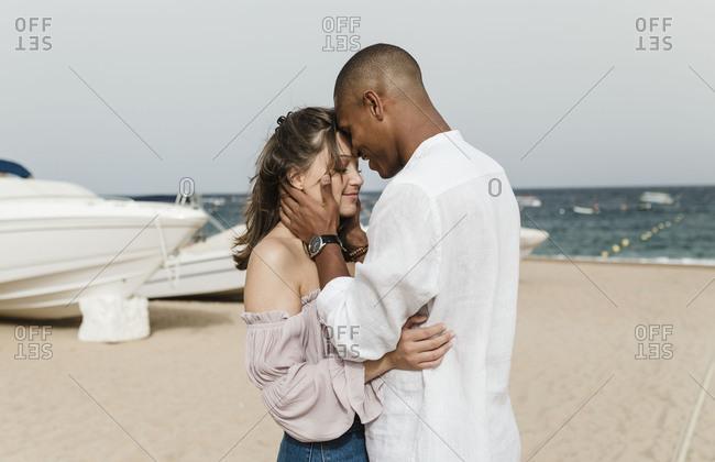An interracial couple affectionately walks on the beach