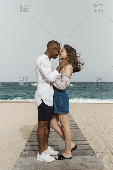 A young interracial couple in love at the beach