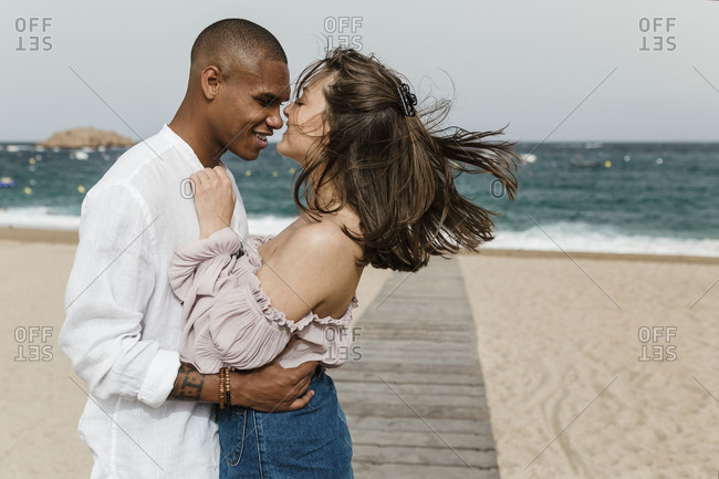 An interracial couple standing face to face on the beach