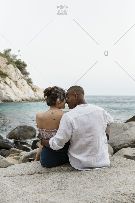 An interracial couple sits on the beach on a rock formation