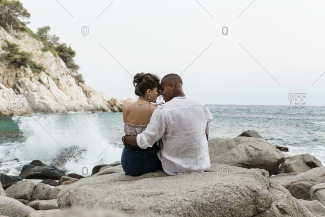An interracial couple sits on a rocky beach